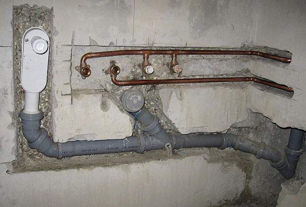 Крепление канализационной трубы к стене закрытым способом монтажа.