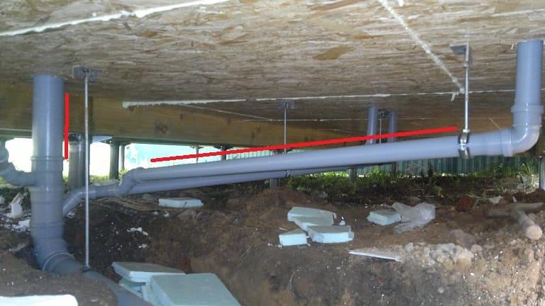 Как устроена под лагами пола канализация в доме на винтовых сваях.