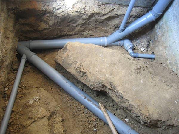 Если рассматривать, как производится укладка канализации под бетонной стяжкой, то изначально это происходит в земле, в рамках фундамента дома.